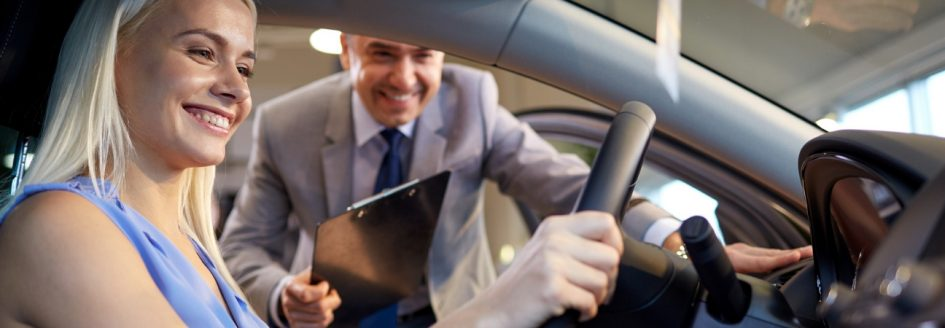 Young woman behind wheel of car at used dealership as salesperson with clipboard looks on